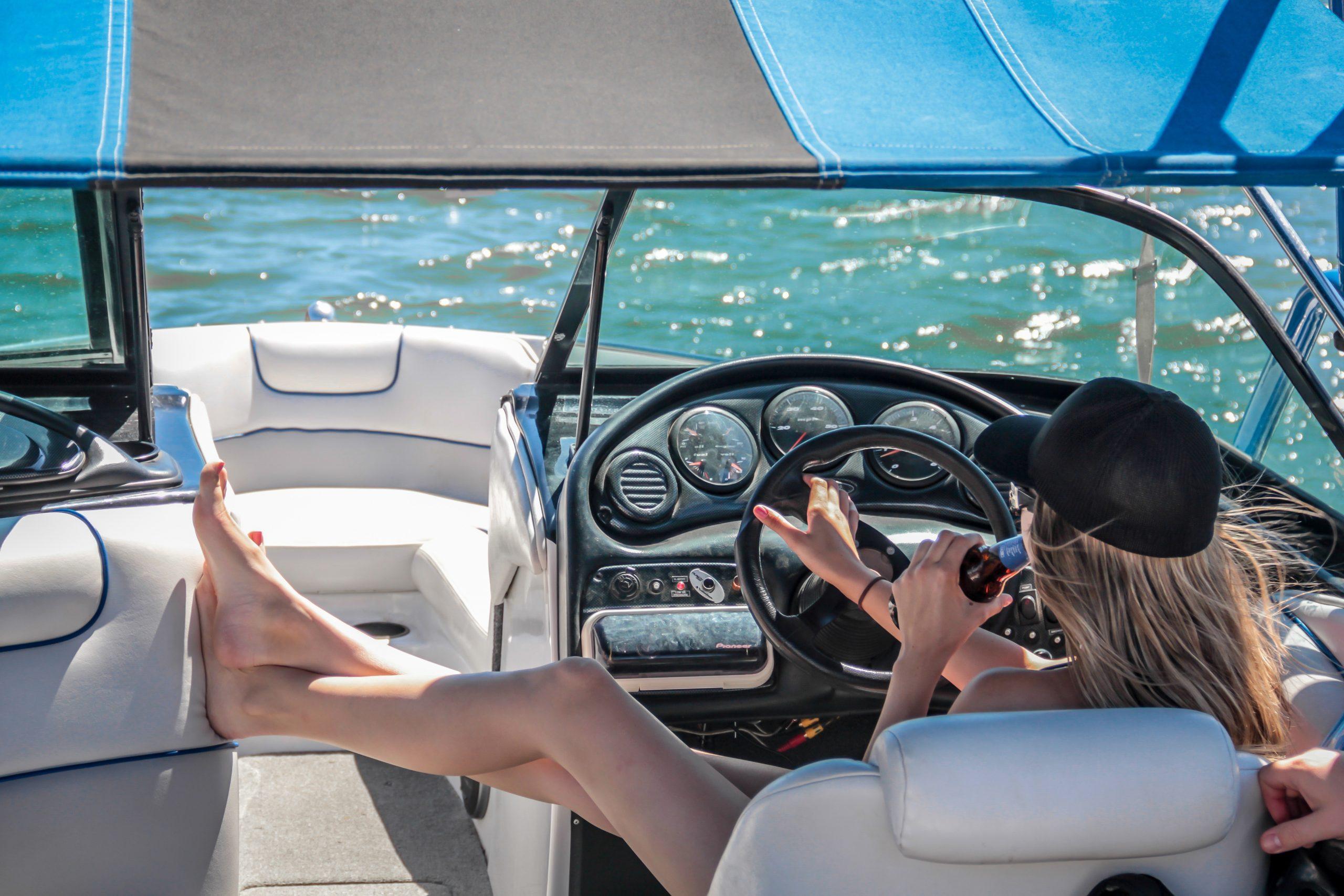 woman-wearing-black-cap-holding-bottle-on-white-speedboat-209978